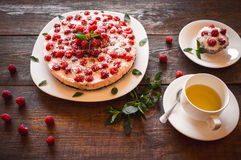 Vegetarian desserts and herbal tea. Appetizing vegetarian pie from protein jelly with fresh berries of raspberry and a cup with green tea. Healthy food. Wooden royalty free stock images