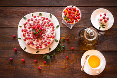 Vegetarian desserts and herbal tea. Appetizing vegetarian pie from protein jelly with fresh berries of raspberry and mint, a teapot and a cup with green tea stock image