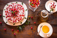Vegetarian desserts and herbal tea. Appetizing vegetarian pie from protein jelly with fresh berries of raspberry and mint, a teapot and a cup with green tea stock images
