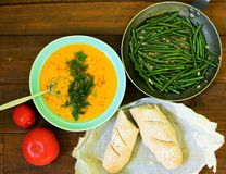 Vegetarian dinner. Creamy pumpkin soup with parmesan and chilli, green beans topped with fried garlic and chilli and whole grain baguette Stock Image