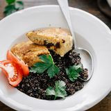 Vegetarian dinner table Plate black quinoa, oatmeal cutlets. Close up plate with black quinoa and oatmeal cutlets with prunes on wooden table. Vegetarian dinner royalty free stock image