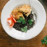 Vegetarian dinner table Plate black quinoa, oatmeal cutlets, tom. Vegetarian dinner table. Plate with black quinoa and oatmeal cutlets with prunes on wooden royalty free stock photos