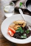 Vegetarian dinner table Plate black quinoa, oatmeal cutlets, water lemon. Close up plate with black quinoa and oatmeal cutlets with prunes on wooden table with stock images