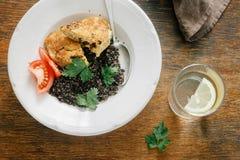 Vegetarian dinner table Plate black quinoa, oatmeal cutlets, water lemon. Vegetarian dinner table. Plate with black quinoa and oatmeal cutlets with prunes on royalty free stock photos
