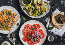 Vegetarian dinner table -  quinoa and pumpkin salad, tomatoes, eggplants and peppers on the grill. On a dark background, top view. Stock Image