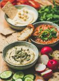 Vegetarian dips hummus, babaganush, muhammara over wooden background Stock Photography