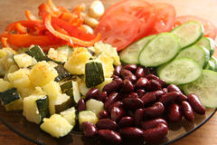 Vegetarian dish. Beans, fried marrows, fresh tomatoes and cucumbers Stock Image