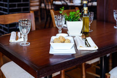 Vegetarian dish of balls of fried potatoes at the restaurant. Dish of potato balls, cutlery, napkins and wine glasses on a wooden table in a restaurant stock photos