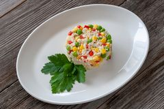Vegetarian dish: a dish of boiled rice, corn, green peas and sweet pepper. stock photo