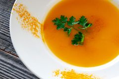 Vegetarian dish. Pumpkin soup with carrots, onions, garlic, olive oil, salt, coconut milk in a white plate decorated with curry s stock image