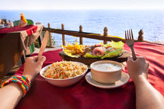 Vegetarian dishes near the ocean. Indian vegetarian sizzler, corn soup and fried rice on the table with ocean at the background. Hands with fork and knife on the royalty free stock photography