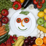 Vegetarian eating smiling face from vegetables and fruits on pla Stock Photos