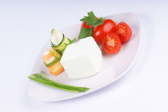 Vegetarian food. Cream cheese, Piccadilly tomatoes, zucchini and carrot rolls with cream cheese finely disposed on a white plate Royalty Free Stock Image