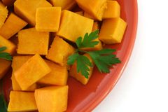 Vegetarian food. Top view of cooked pumpkin pieces on red plate stock photography
