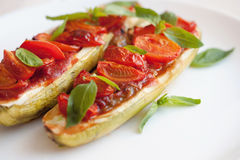 Vegetarian food. Baked zucchini with tomato and basil Stock Images