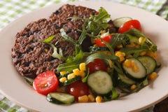 Vegetarian food: black bean burgers and a salad of fresh vegetab Royalty Free Stock Photo