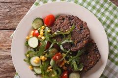 Vegetarian food: black bean burgers and a salad of fresh vegetab Royalty Free Stock Image