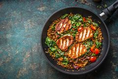 Vegetarian food concept. Healthy lentil dish with spinach and fried cheese in cooking pan on rustic background with ingredients royalty free stock images