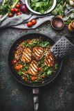 Vegetarian food concept. Healthy lentil meal with spinach and fried cheese in cooking pan on rustic background with ingredients. Top view Stock Image