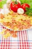Vegetarian food. farfalle with fresh tomatoes. Farfalle with fresh tomatoes and mushrooms Royalty Free Stock Image