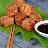 Vegetarian food, fried tofu. Frugal vegetarian food from Vietnamese cuisine, fried tofu with spice power, cover with crispy flour, homemade food on green leaf stock image