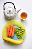Vegetarian food and green tea on white table. Carrot, banana and kiwi on a plate for a lunchtime or afternoon snack. Vegetarian food and green tea on white Royalty Free Stock Images
