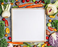 Vegetarian food, health and diet nutrition background with variety of fresh farm vegetables  around a blank white chalkboard, top Stock Images