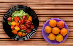 Vegetarian food . healthy food. a salad of spinach, apricot, strawberry on a plate on a wooden background.  stock photography