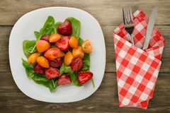 Vegetarian food . healthy food. a salad of spinach, apricot, strawberry on a plate on a wooden background.  royalty free stock image