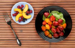 Vegetarian food . healthy food. a salad of spinach, apricot, strawberry on a plate on a wooden background.  stock images