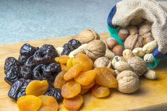 Vegetarian food of nuts and dried fruits on the kitchen board.  stock photography