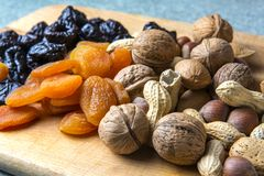 Vegetarian food of nuts and dried fruits on the kitchen board.  stock image