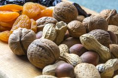 Vegetarian food of nuts and dried fruits on the kitchen board.  stock photos