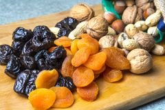 Vegetarian food of nuts and dried fruits on the kitchen board.  royalty free stock photo