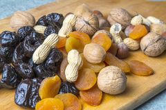 Vegetarian food of nuts and dried fruits on the kitchen board.  royalty free stock photography