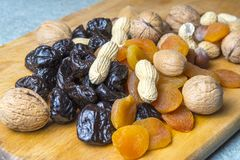 Vegetarian food of nuts and dried fruits on the kitchen board.  stock photo