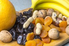 Vegetarian food of nuts and dried fruits on the kitchen board.  royalty free stock photos
