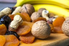 Vegetarian food of nuts and dried fruits on the kitchen board stock image