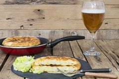 Omelette with a glass of beer. Vegetarian food, omelette in a pan and on a plate with chopped lettuce, a glass of beer stock photo