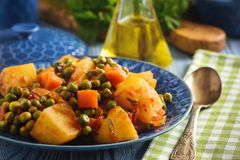 Vegetarian food - potatoes with pea and tomatoes, greek style cuisine. royalty free stock photo