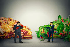 Vegetarian food representative fighting unhealthy junk fatty food guy with boxing gloves Stock Photography