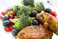 Vegetarian food. Vegetable cutlets from red lentils, onions, parsley and oatmeal. With salad of broccoli, pomegranate seeds and bl. Ueberries a variety of royalty free stock photography