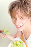 Vegetarian food - woman eating salad Stock Images