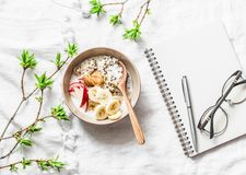 Vegetarian gluten free breakfast - quinoa, coconut milk, banana, apple, peanut butter bowl on light background, top view. Diet pla. N breakfast or snack and Stock Images