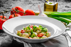 Vegetarian gnocchi with spring onions and tomatoes Royalty Free Stock Images
