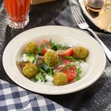 Vegetarian green salad with falafel and glass of tomato juice on the table royalty free stock images