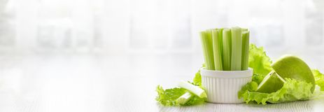 Vegetarian healthy food concept. Green celery, lettuce leaves and aplle. Banner format. Copy space stock photos