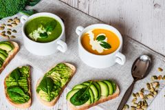 Vegetarian healthy food. Soup and vegan sandwiches. Different sandwiches with avocado. Brunch on white wooden background Royalty Free Stock Images