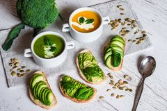 Vegetarian healthy food. Soup and vegan sandwiches. Different sandwiches with avocado. Brunch on white wooden background Stock Photos