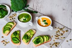Vegetarian healthy food. Soup and vegan sandwiches. Different sandwiches with avocado. Brunch on white wooden background Royalty Free Stock Photography